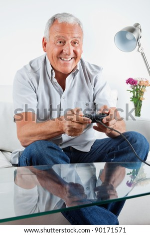 Happy senior man playing video game at home - stock photo