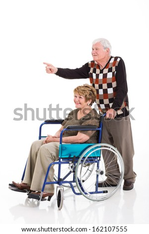 happy senior man pointing while his handicapped wife on wheelchair - stock photo