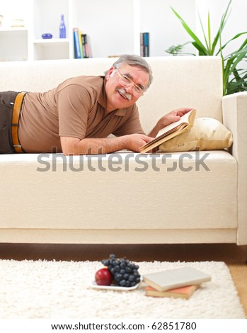 Happy senior man relaxing and reading books on sofa