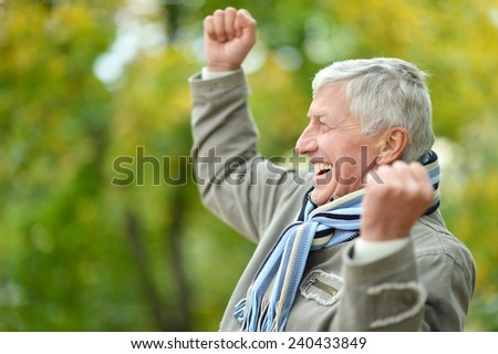 Happy Senior man resting in the park in autumn - stock photo