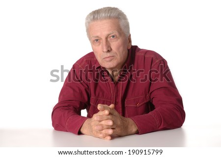 Happy senior man sitting at table on white background