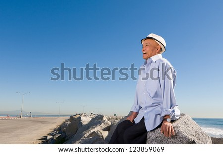 Happy Senior Man sitting on Rocks on the Beach