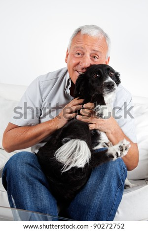Happy senior man sitting on sofa with his dog at home - stock photo
