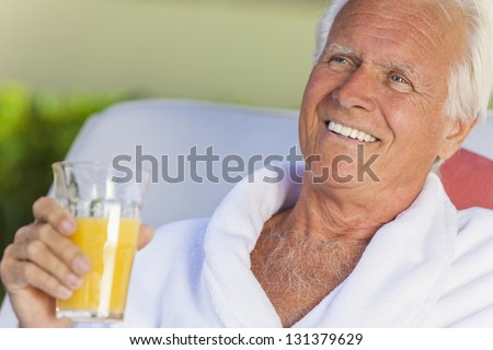 Happy senior man sitting outside wearing bathrobes at a health spa drinking orange juice