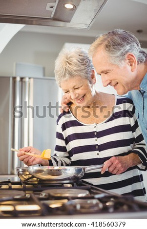 Happy senior man standing with wife cooking food at hob in kitchen - stock photo