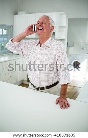 Happy senior man talking on mobile phone while standing in kitchen