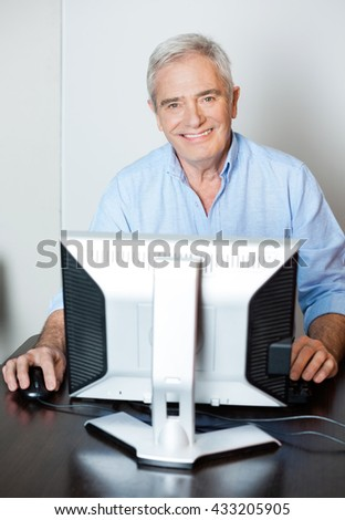 Happy Senior Man Using Computer In Class