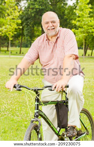 Happy senior man with bike in the park.
