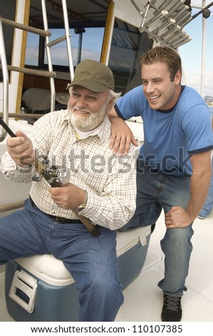Happy senior man with grandson fishing together on yacht - stock photo