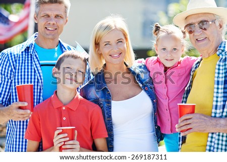 Happy senior man with his children and grandchildren looking at camera  - stock photo