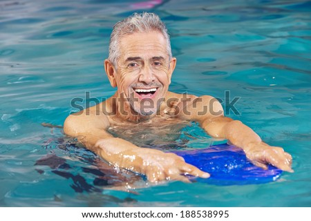 Happy senior man with kickboard in water of swimming pool - stock photo