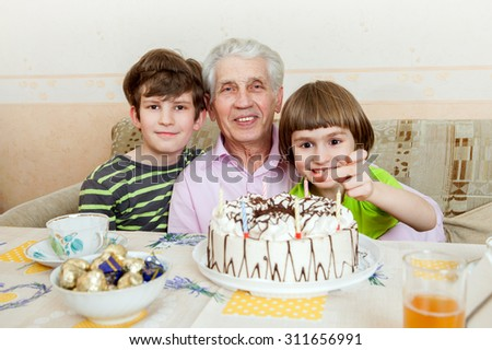 happy senior man with two grandchildren sit at the holiday cake.