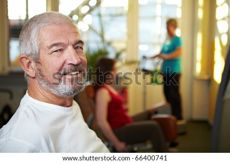Happy senior man working out in a gym - stock photo