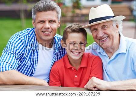 Happy senior man, young man and boy looking at camera  - stock photo