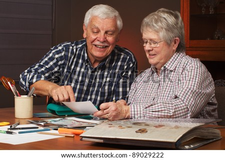 Happy senior married couple sharing memories while  working on family photo  album together. Horizontal format. - stock photo