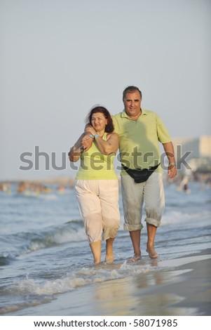 happy senior mature elderly people couple have romantic time on beach at sunset - stock photo