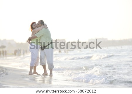 happy senior mature elderly people couple have romantic time on beach at sunset - stock photo
