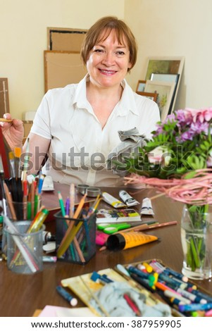Happy senior mature woman painting for fun with paints at home - stock photo