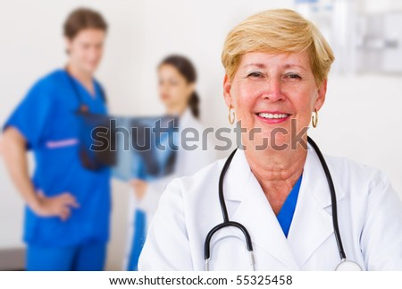 happy senior medical doctor, background is her young colleagues looking at x ray - stock photo
