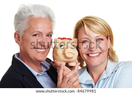Happy senior mother and adult daughter holding a piggy bank - stock photo