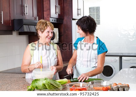 happy senior mother and middle aged daughter cooking in kitchen - stock photo