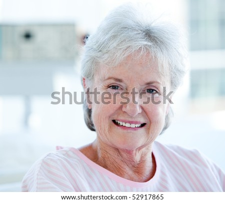 Happy senior patient sitting on a wheelchair in a hospital - stock photo