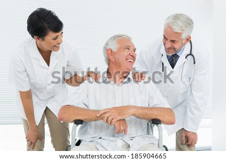 Happy senior patient with doctors sitting in wheelchair at the hospital - stock photo