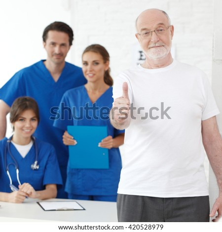 Happy senior patient with thumbs up and his doctors - stock photo