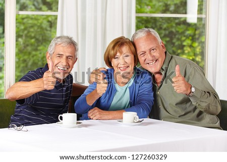 Happy senior people holding thumbs up while drinking coffee in retirement home - stock photo