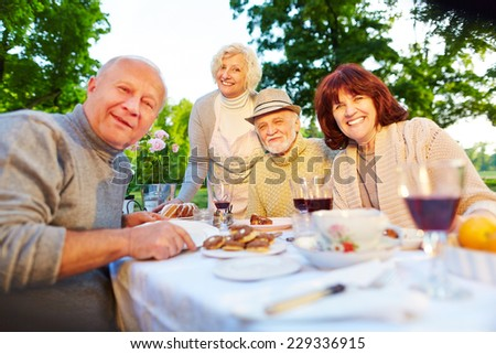 Happy senior people sitting at set coffee table in a summer garden - stock photo