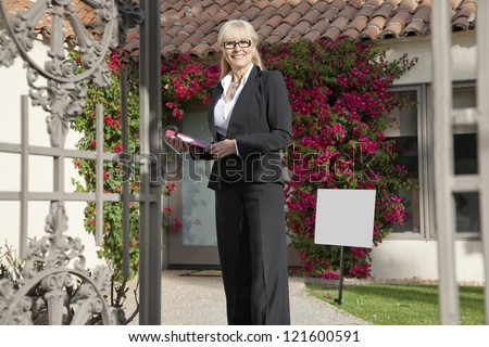 Happy senior real estate agent standing in front of house
