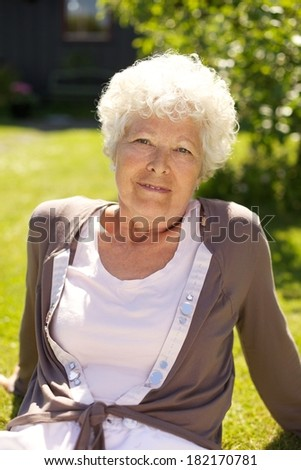 Happy senior sitting on the grass and looking at camera on a sunny afternoon - stock photo