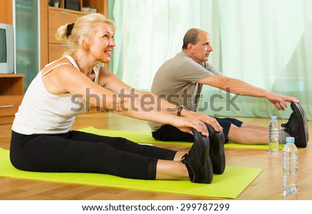 Happy senior spouses warming up muscles before exercising 