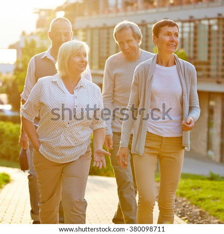 Happy senior travel group walking in a city in summer - stock photo