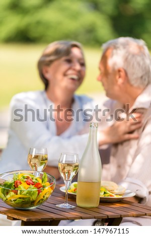 Happy senior wife and husband dining outdoors - stock photo