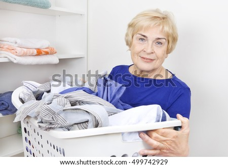 Happy senior with basket full od clothes
