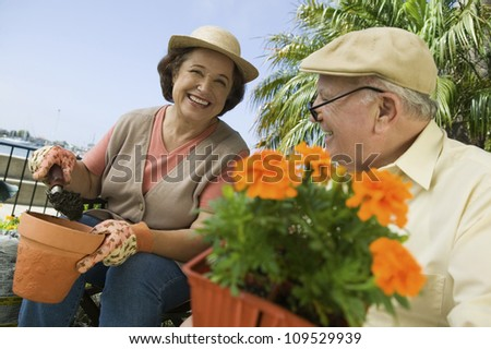 Happy senior woman and man working in the garden - stock photo