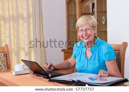happy senior woman calculating her finance at home - stock photo