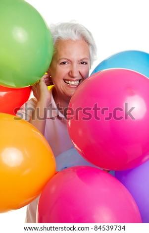 Happy senior woman celebrating with many balloons - stock photo