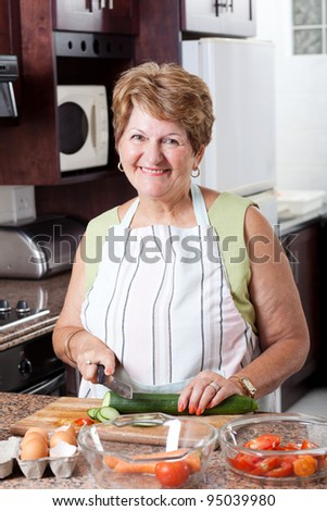 happy senior woman cooking in kitchen