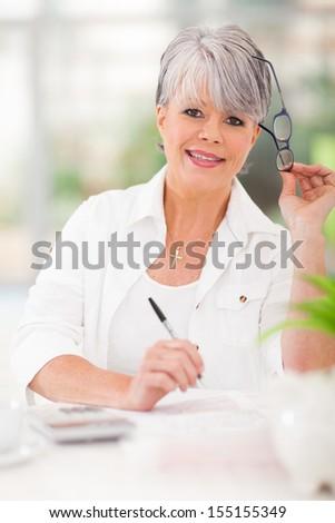 happy senior woman doing home finances - stock photo