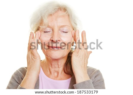 Happy senior woman doing skin care for her face - stock photo