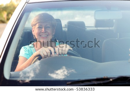 happy senior woman driving a car - stock photo