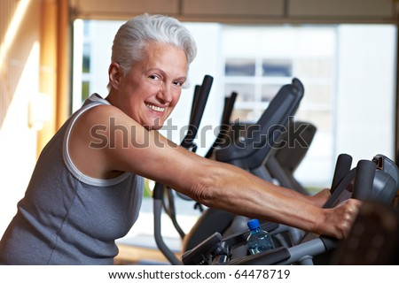 Happy senior woman exercising on bike in gym