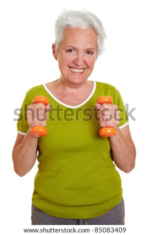 Happy senior woman exercising with two dumbbells - stock photo