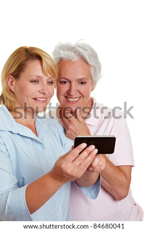 Happy senior woman getting a smartphone explained - stock photo