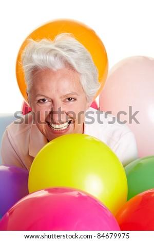 Happy senior woman having fun with colorful balloons - stock photo