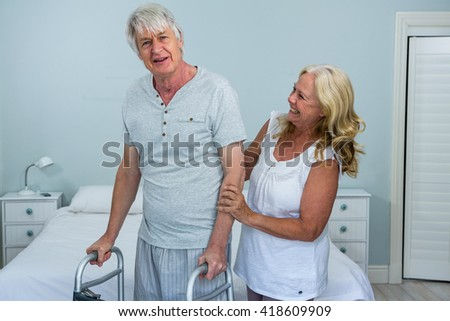Happy senior woman helping man to walk in bedroom at home - stock photo