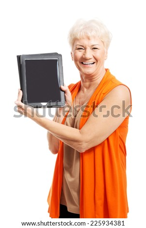 Happy senior woman holding a tablet - stock photo