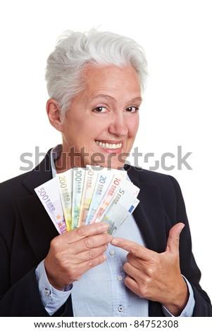 Happy senior woman holding Euro money fan - stock photo